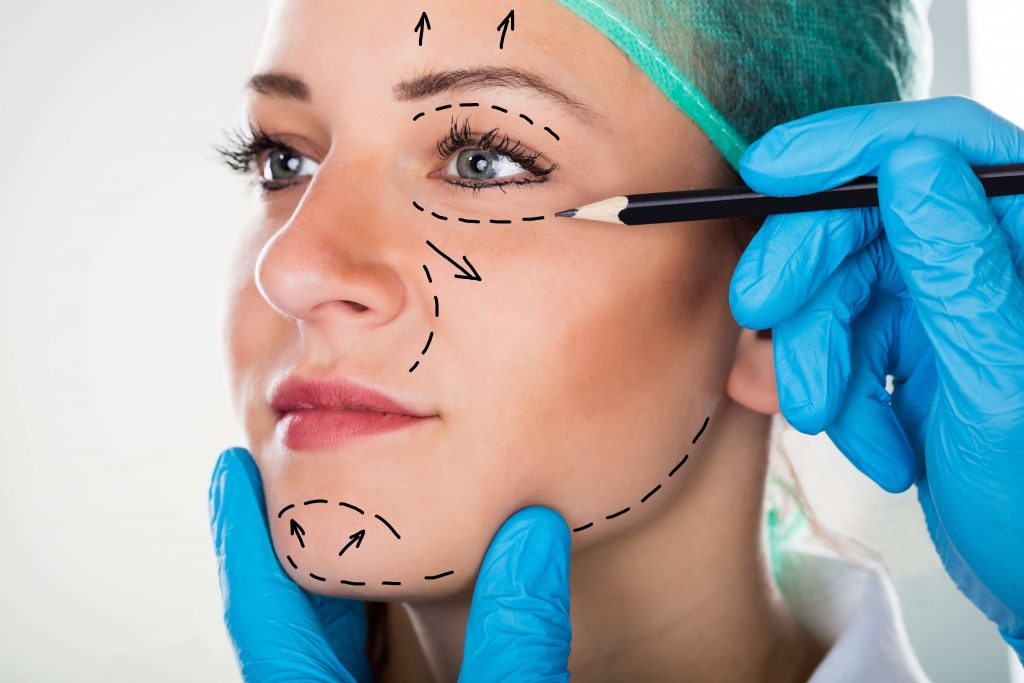 Foto doutor desenhando rosto de uma mulherpara cirurgia de rejuvenescimento facial
