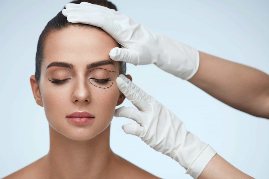 Foto doutor tocando rosto de mulher demonstrando Blefaroplastia