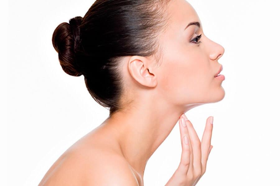 Mulher tocando o pescoço demonstrando o procedimento de Lipoaspiração de Pescoço